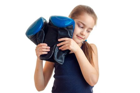 pugilist: sweet girl holding a big boxing gloves is isolated on a white background
