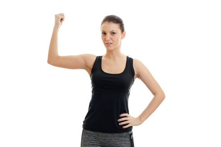 young cute fitness girl in black shirt looks into the camera and keeps one hand on the top of isolated on white background