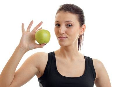Portrait of a beautiful young girl who holds in hand a Green Apple and looking at camera isolated on a white background close-up