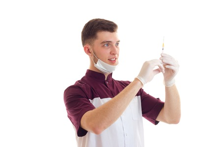 laboratorian: young smiling laboratorian with the mask on the face lifted into the syringe is isolated on a white background Stock Photo