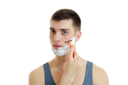 smile close up: charming young guy looks into the distance and shaves his beard with a foam machine is isolated on a white background close-up