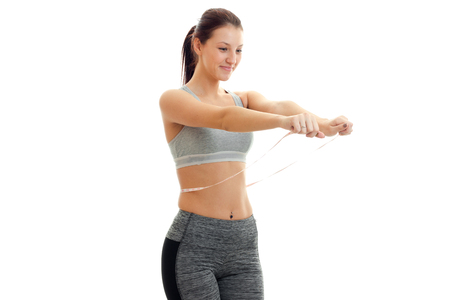 smiling cute girl in grey top stretched her hands forward and keep the measuring tape at the waist is isolated on a white background Stock Photo