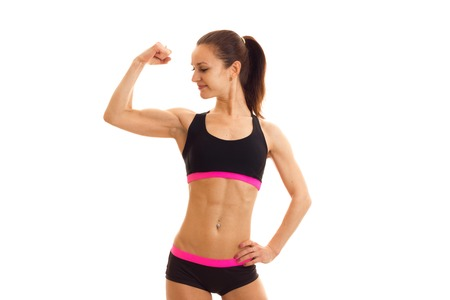 Slim young girl in sportswear looks at his muscle on hand isolated on white background Stock Photo