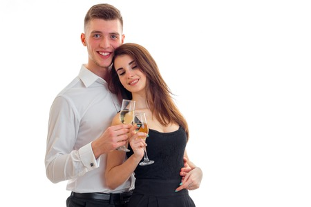 white wine: beautiful young girl smiling closing her eyes stands next to a cute guy and they are holding wine glasses isolated on white background Stock Photo