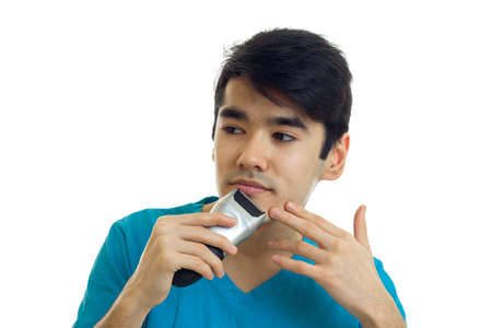 handsome young guy in a t-shirt looking sideways and shaves a beard trimmer close-up isolated on white background