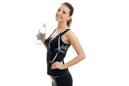 cheerful young fitness girl in black suit stands sideways smiles and holding a bottle of water and a measuring tape on the neck isolated on white background. Stock Photo