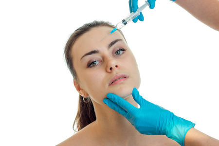 cosmetologist in blue gloves keeps hand face of a young girl and introduces injection close-up isolated on white background