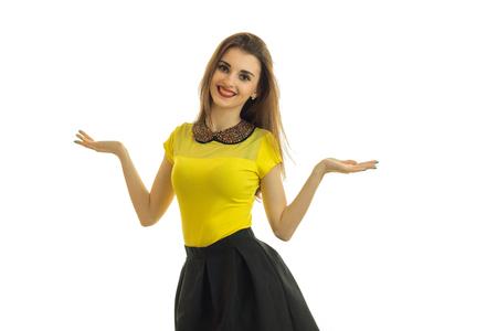 明るい服でかわいいピンを開く女の子はまっすぐ笑顔を立ち上分離の白い背景の両側にあなたの手の手のひらを保持しています。