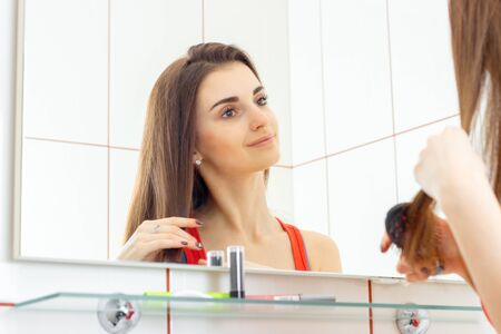 flyaway: cute smiling young girl stands in front of a mirror and combing her long hair closeup