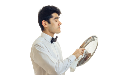 young cute waiter stands sideways and gently rub until luster ware tray is isolated on a white background Stock Photo