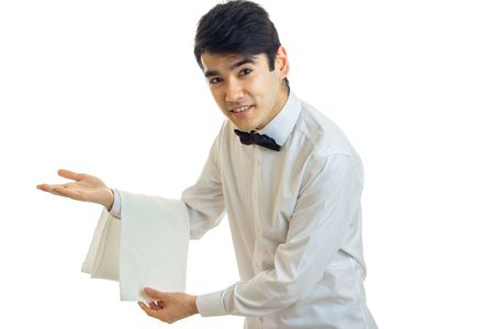 silver: handsome young waiter invites guests to the table and smiling isolated on white background Stock Photo