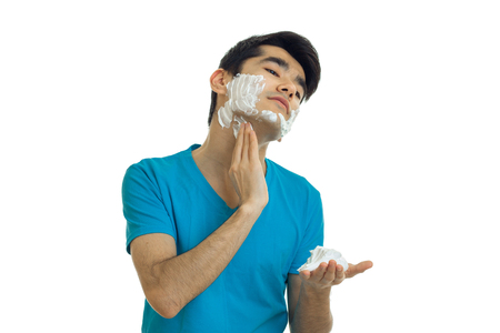 young handsome guy in the blue shirt tilted his head and putting a face shaving foam isolated on white background Stock Photo
