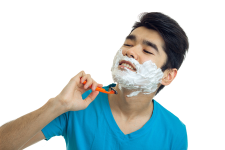 charming, charming guy tilted head closed his eyes and shaves his beard machine is isolated on a white background close-up