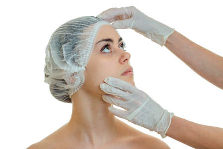 dermatologist examines the face of a young girl in white gloves close-up isolated on white background
