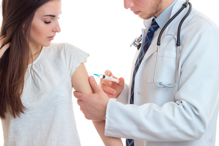 paciencia: the doctor makes an injection syringe on the shoulder of a young girl have close-up isolated on white background