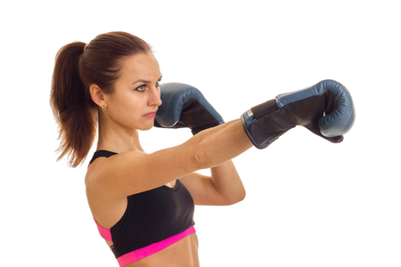 a young girl with the ponytail looks toward and reaches out his hands forward in boxing gloves is isolated on a white background Stock Photo