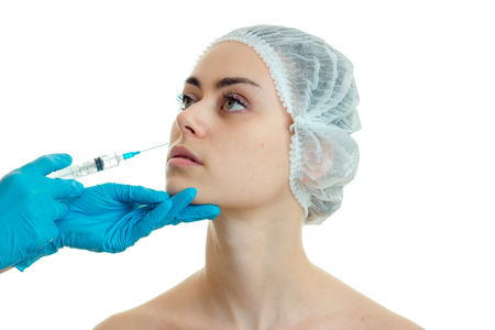 cosmetologist introduces vaccine against wrinkles on the face of a young girl in a special Cap close-up isolated on white background Stock Photo