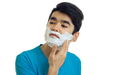 narcissistic: beautiful narcissistic guy looks away and putting a beard foaming close-up isolated on white background Stock Photo