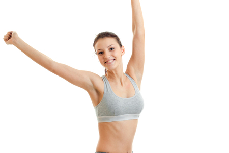 bakground: Cheerful sports girl smiling on camera with hands up in the air isolated on white bakground