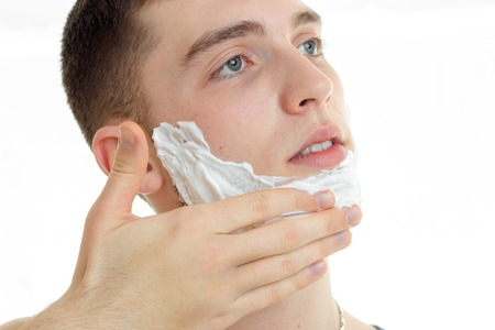bakground: close up portrait of young handsome man with shaving cream on his face isolated on white bakground Stock Photo