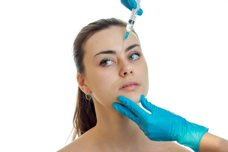 dermatologist in blue gloves makes injection on the face of a young pretty girl close-up isolated on white background