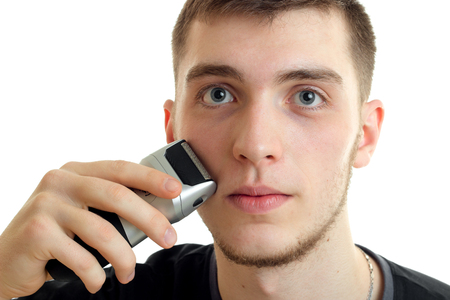 Portrait of a handsome young guy who shaves face machine and looks into the camera close-up isolated on white background Stock Photo