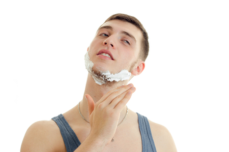 close your eyes: horizontal portrait of a young handsome guy with foam on his face that shaves close your eyes is isolated on a white background