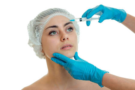 cosmetologist in gloves conducts procedures on the face of the girl with the help of injections is isolated on a white background close-up