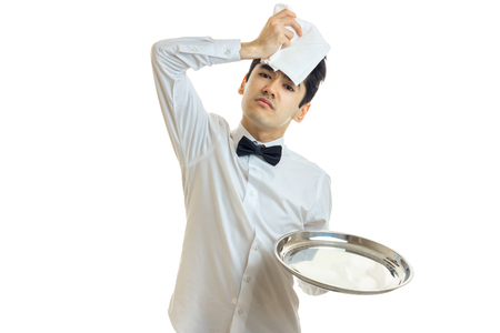 the young weary waiter appended to the head cloth and holding a tray of isolated on white background Stock Photo