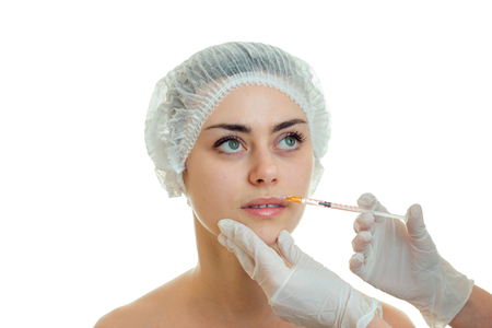 doctor gloves introduces vaccine on the face of a young beautiful girl isolated on a white background close-up