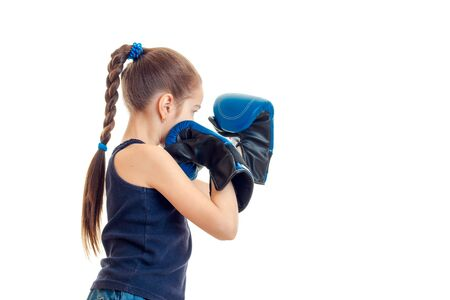 pugilist: little girl in blue sports gloves practicing boxing isolated on white background Stock Photo