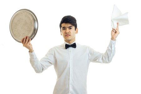Surprised brunette man waiter with tray and servet in his hands looking at the camera isolated on white background