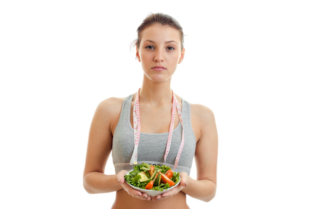 eats: beautiful woman with measure tape on her neck eats salad isolated on white background