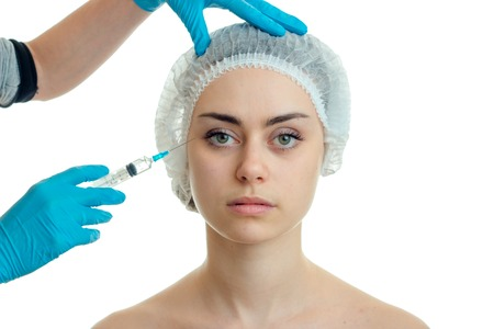 woman makes prick in face plastic surgeon isolated on white background