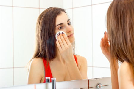woman in bath: a woman washes the makeup in the bathroom front of the mirror