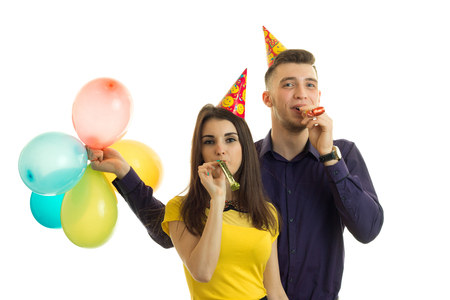 25s: couple on birthday party having fun and blowing horns isolated on white background