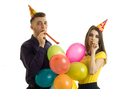 25s: funny couple blowing horns at birthday party isolated on white background