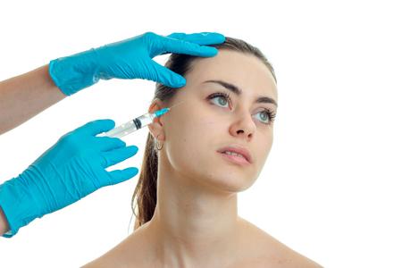 inyeccion intramuscular: Una mujer hace un pinchazo en la cara por un médico en el estudio Foto de archivo
