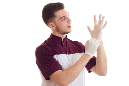 doctor in special clothes puts on white gloves hands isolated on white background close-up