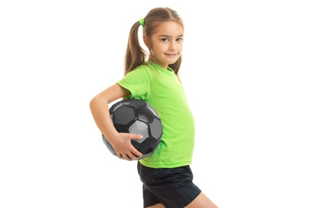Petite athletic girl with giant holding a ball and smiling isolated on white background