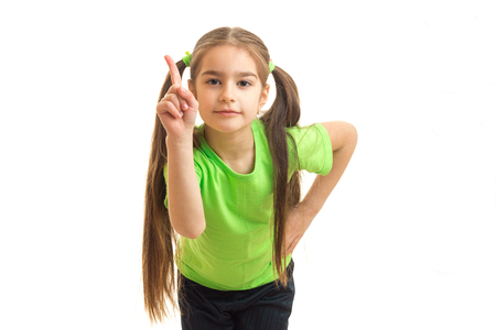 little girl with tails and bright t-shirt posing in the Studio and shows finger is isolated on a white background