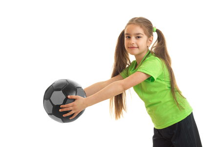 Petite athletic girl stretches the ball in her hands and smiling isolated on white background