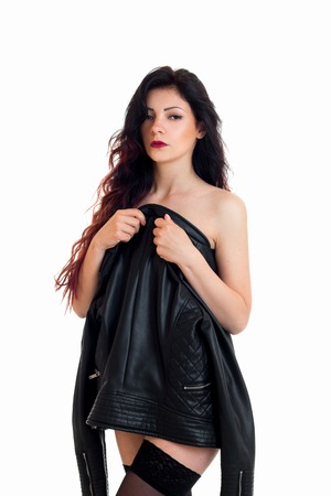 shy brunette woman hide her body behind a leather jacket and looking at the camera isolated on white background