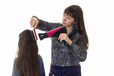 hair stylist: adult woman stylist makes a hairstyle to a little girl with long hair isolated on white background