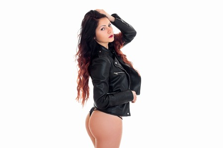 young girl in leather jacket stands sideways in g-strings with big isolated on white background