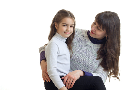 portrait of adult mother with her little daughter in studio isolated on white background