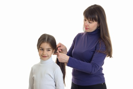 Volwassen moeder maakt een kapsel aan haar kleine dochter die op een witte achtergrond wordt geïsoleerd
