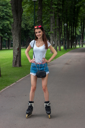 Skinny lucky girl riding in the Park, rollerblading and keeps your hands on the sides