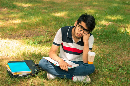 young cute guy got tired sitting on the grass with a book Stock Photo