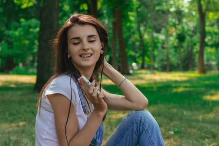 Portrait of a cheerful beautiful brunette who sits in the Park closes her eyes and listens to music with headphones Stock Photo